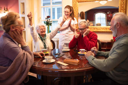 Older woman wins in a domino game and celebrates it with raising her arms