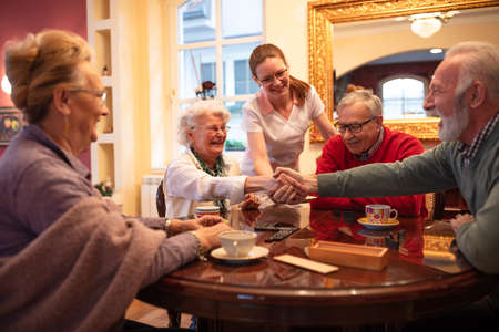 Older folks shaking hands over a game result while sitting at the table