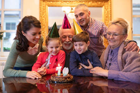 Happy family wishing happy birthday to their oldest member Banque d'images