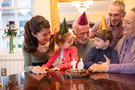 Happy family wishing happy birthday to their oldest member