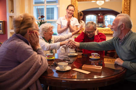 Older folks shaking hands over a game result while sitting at the table Imagens