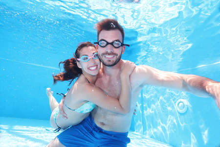 Woman holding to her man while they dive in the swimming pool Stockfoto