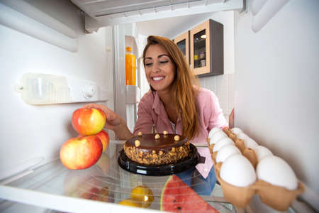 Pretty young woman having food related doubts, will it be an apple or a cake, observed from the fridge concept