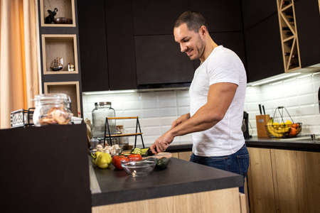 Young muscular man slicing various vegetables and preparing them for a tasty salad he is about to make in his kitchen