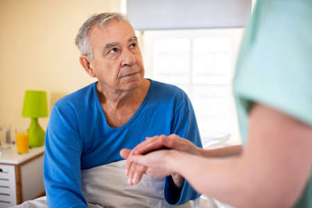 Caring nurse holding a hand of a senior man occupant in a nursing home room, providing care for the elder concept Banco de Imagens