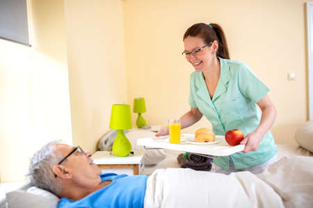 Nurse in a old people's home providing residential care by bringing breakfast to her senior man occupant, care for the elder concept Foto de archivo