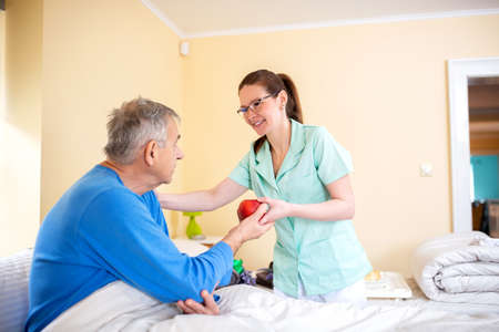 Senior man attended by a nurse in a elder folks home, senior people care concept