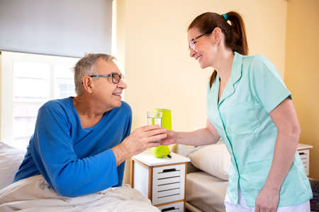 Loving nurse handing glass of water to her nursing occupant in a elder peoples home, elder people assistance concept