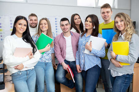 Young people in classroom posing for a picture together, student concept