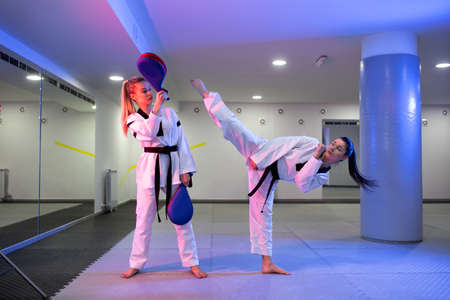 Two young girls training taekwondo with one coaching the other