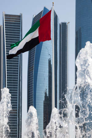 Flag of the UAE in front of skyscrapers in Abu Dhabi photo