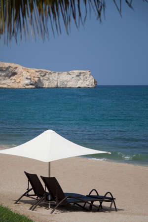 loungers: two chaise loungers and white parasol on the beach in front of a blue sea