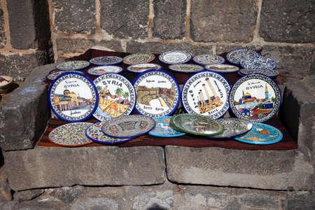 divan: Touristische Keramikplatten in Bosra auf einem grauen Stein Diwan