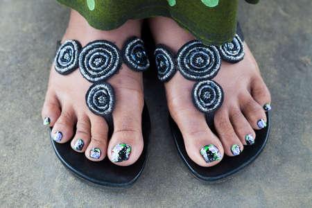 painted toenails: black green violet painted toenails of women feet in flip flops