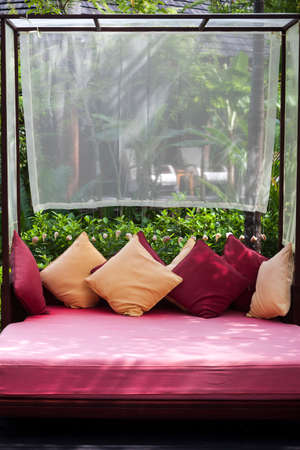 daybed: Large wooden framed canopy bed with colourful red and yellow cushions Stock Photo
