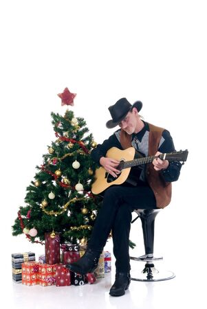 Christmastree with presents and cowboy playing on his guitar, white background  photo