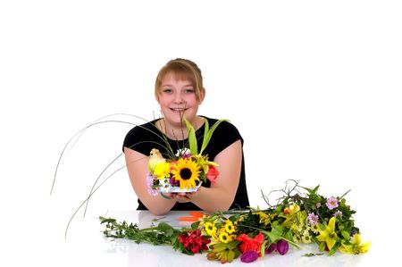 Young girl arranging flowers on reflective surface, white background, studio shot Stock Photo - 4739841