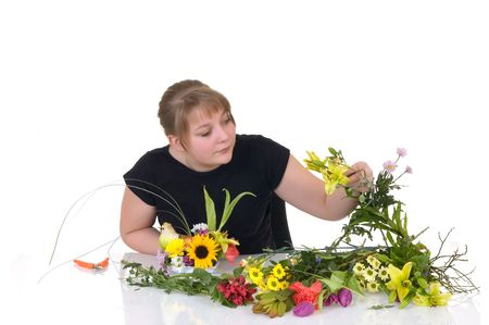 Young girl arranging flowers on reflective surface, white background, studio shot photo