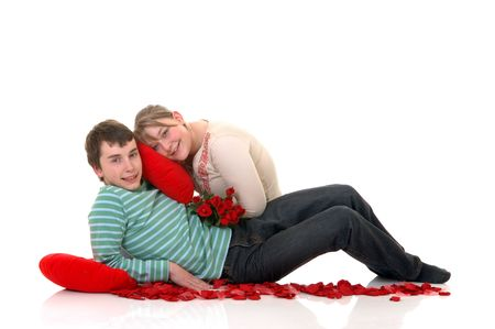 Two casual dressed teenagers, teenage man and woman in love, surrounded with rose petals. studio shot. photo