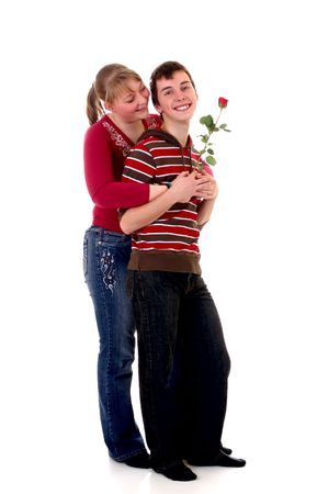 Two casual dressed teenagers , teenage man holding rose flower and woman in love. studio shot. photo