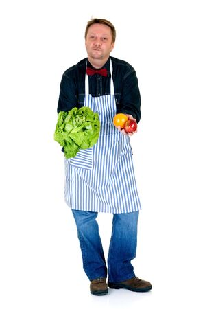 Happy cook showing some fresh vegetables and fruits on white background, reflective surface  photo