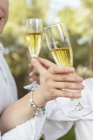 Toast with glasses of champagne from an outdoor couple in which only their hands can be seen