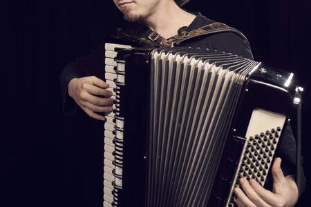 Detail of hands playing an accordion instrument on black background