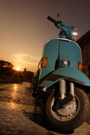 vespa piaggio: Vespa parcheggiata vicino al lago al tramonto  Archivio Fotografico