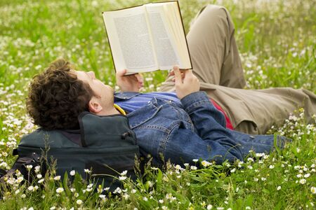 field study: guy laying on the grass and reading a book