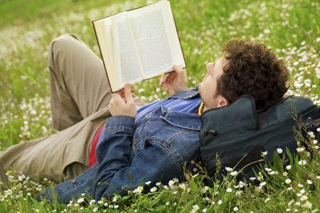 boyfriend: individuo que pone en la hierba y que lee un libro Foto de archivo