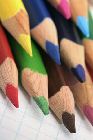 coloured pencils with pointed tips on a squared exercise book