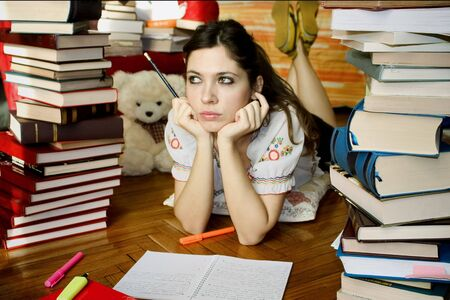 Girl studying surrounded by books photo