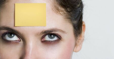 girl looking up to a yellow post it sticked on her forehead. You can write whatever you want over it...