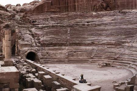 colonisation: ragazza che osserva fino ad un teatro antico Archivio Fotografico