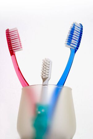 family of toothbrushes in a cup isolated against white! photo