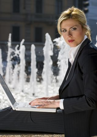 girl sitting alone on a wall and working with her laptop photo