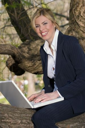 girl sitting alone on a tree and working with her laptop photo