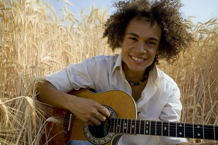 cool guy sitting in a cornfield playing guitar Stock Photo - 446255