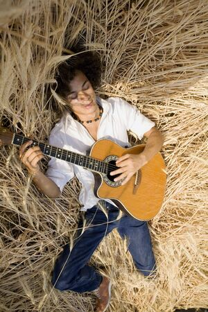 cool guy laying in a cornfield playing guitar Stock Photo - 450015