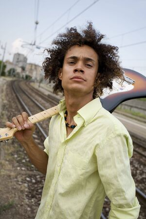cool guy with his guitar at a train station Stock Photo - 450024