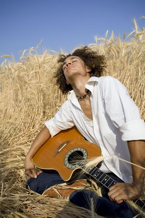 cool guy laying in a cornfield playing guitar Stock Photo - 450039