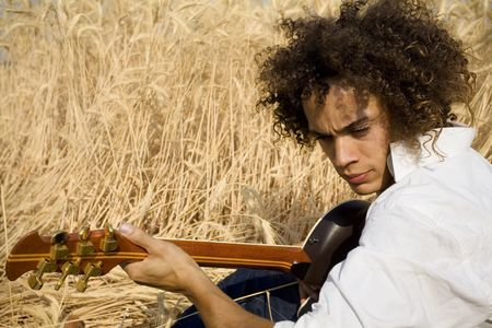 cool guy laying in a cornfield playing guitar Stock Photo - 450041