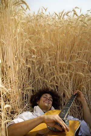 cool guy laying in a cornfield playing guitar photo