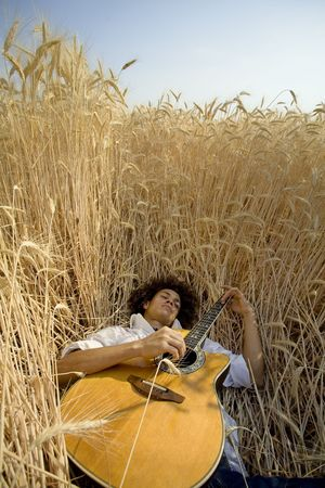cool guy laying in a cornfield playing guitar Stock Photo - 456357