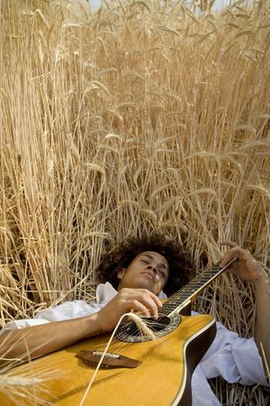 cool guy laying in a cornfield playing guitar Stock Photo - 459817