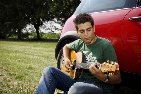 cool guy: cool guy playing guitar besides his car