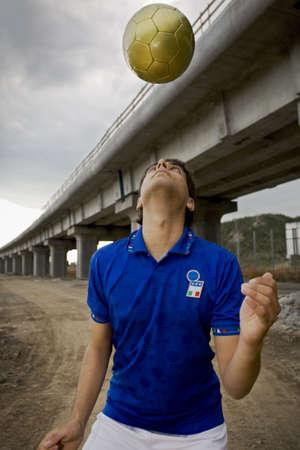 jugando futbol: chico jugar al f�tbol bajo un puente  Foto de archivo