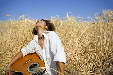 cool guy laying in a cornfield playing guitar Stock Photo - 476573