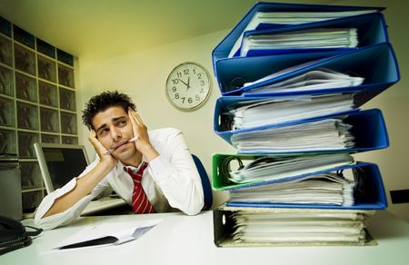 exhausted businessman surrounded by files photo