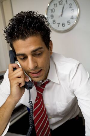 annoyance: young businessman talking on the phone in his office